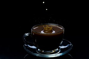 Drops of milk fall into a glass cup with black coffee, black background