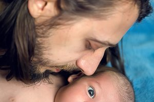 father long hair kissing his son