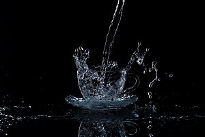 Water pours into the cup on a black background, studio light