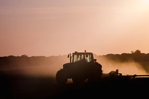 Silhouette of tractor working