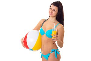 Woman in swimming suit holding cocktail and ball