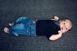 newborn baby lying in blue jeans and a black scarf
