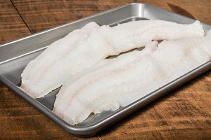 Fillets of cod fish on baking pan