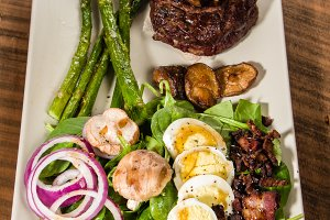 Steak and spinach salad on white plate