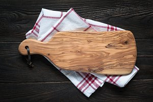 Cutting board on dark wooden table.