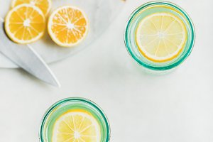 Detox lemon water in glasses, top view, copy space