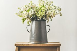Spring bouquet of white lilacs in vintage gray enamel vase