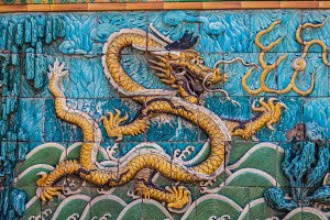 Golden dragon with white crest floating in waves