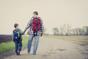 Father and son walking on the road