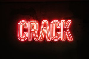 Neon sign on a broken wall.