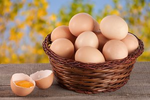 eggs in a wicker basket on a wooden board with blurred garden background