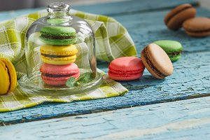 Green, pink and yellow french macarons under the glass on the wooden boards