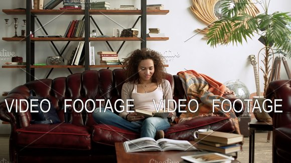 Young Happy Latin Woman Read Paper Book For Education Sitting Alone On Comfort Leather Sofa