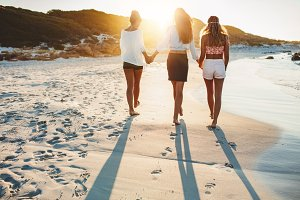 Three friends walking on the beach