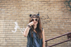 Bad sexy woman with leather cat ears showing her finger mustache.