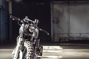 motorcycle standing in dark building in rays of sunlight