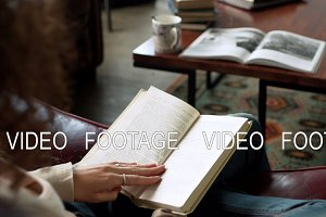 close up view of paper book in hands of latin young woman who read it, sitting on leather sofa