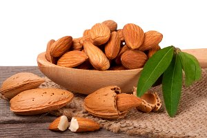 heap of peeled almonds with leaf in a wooden spoon on table isolated white background