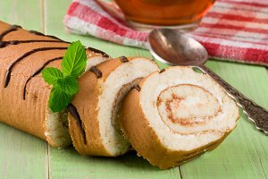 Biscuit swiss roll on green wooden background
