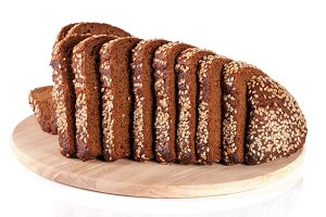 slices of black bread with sesame seeds on a cutting board isolated on white background