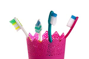 Toothbrushes in pink glass isolated on white background