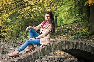 girl sitting on stone bridge