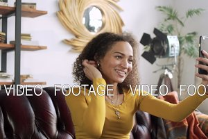 young happy latin woman using mobile phone for video chat online and blogging for social media