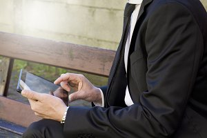 Businessman sitting in the park using tablet