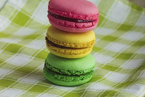 Yellow, green and pink macarons on the plaid napkin