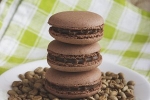 Brown macarons on the plate with green coffee beans