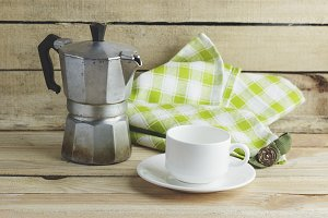 Cup on the saucer, coffee pot and plaid napkin, wooden background