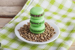 Green macarons on the plate with green coffee beans