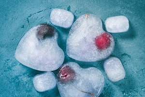 Heart shaped ice cubes with frozen cherry