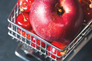 Fresh red fruit berries supermarket cart on black