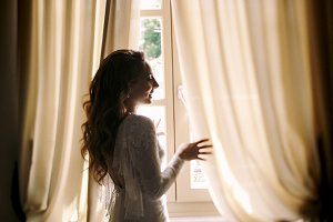 Bride stands between beige curtains