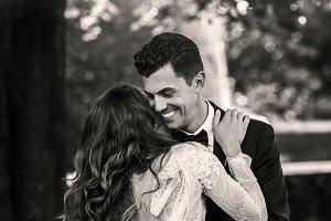 Handsome groom hugs curly bride
