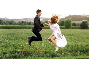 Bride and groom jump high