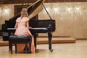 Cute teenager girl plays piano in the concert hall at scene