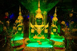 Green and golden buddhas sitting in the temole.