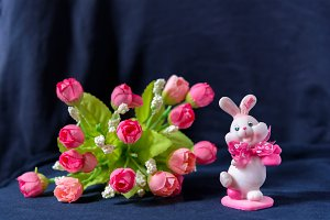 Valentines day pink bunny souvenir with rose bouquet on black background