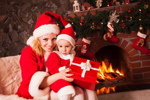 Mother and son near Christmas fireplace