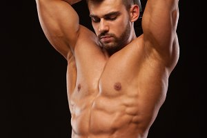 Strong man making exercises on triceps with a dumbbell. Close up shot training hands. Fitness Model showing his Torso with six pack abs. isolated on black background with copyspace
