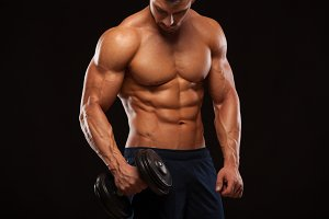Handsome power athletic man with dumbbell is confidently looking forward. Strong bodybuilder with six pack, perfect abs, shoulders, biceps, triceps and chest Isolated on black background with copyspace
