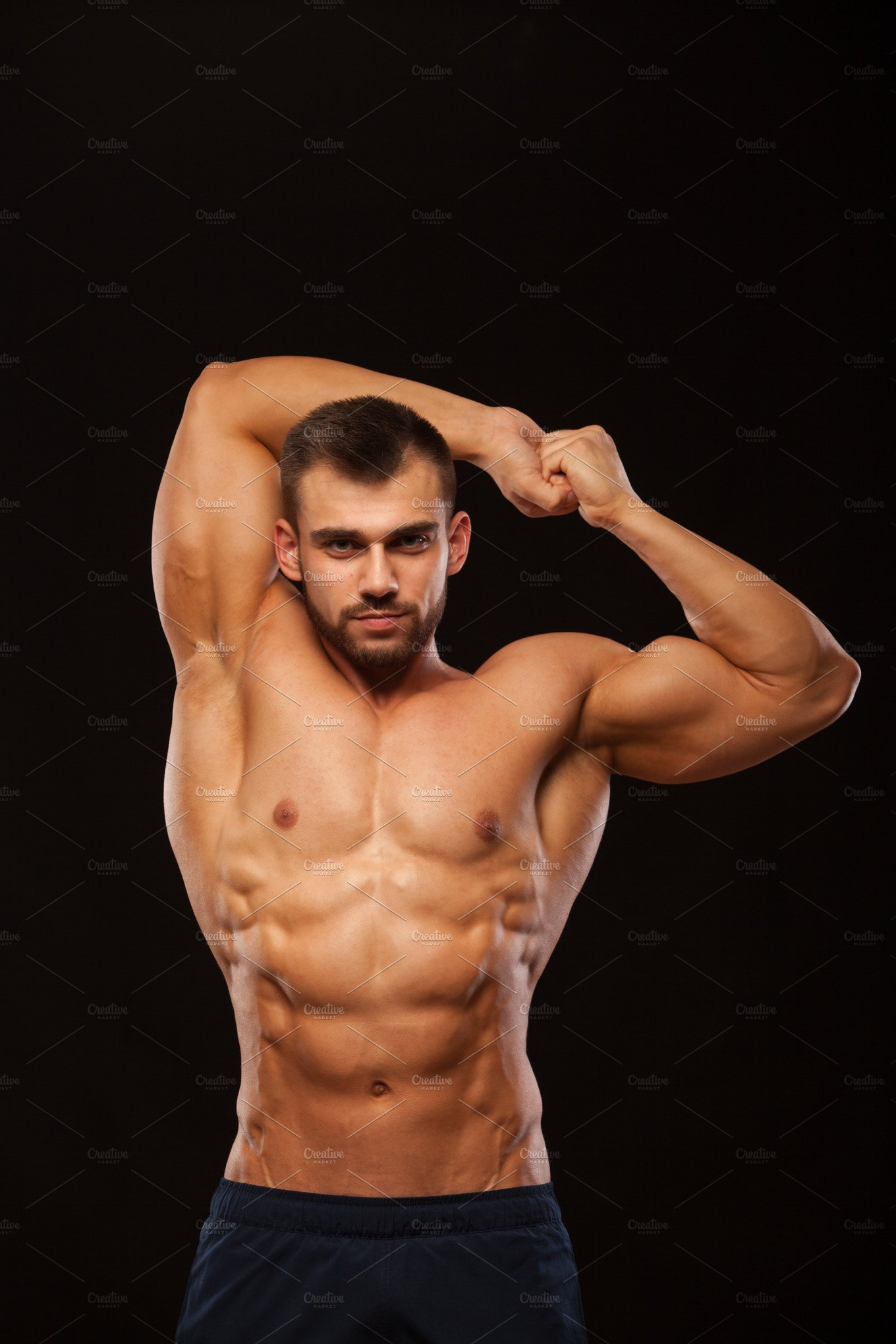 Strong athletic man fitness model is showing his torso