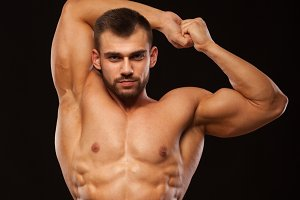 Strong Athletic Man - Fitness Model is showing his Torso with six pack abs and holding his hands up. isolated on black background with copyspace