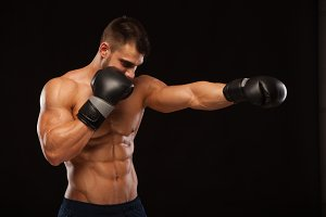 Muscular young man with perfect Torso with six pack abs, in boxing gloves is showing the different movements and strikes isolated on black background with copyspace
