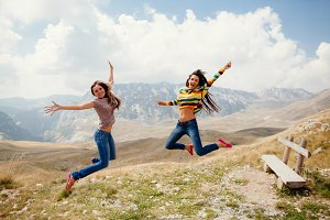 women travel and jump together