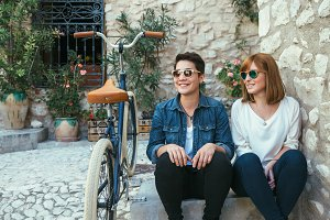 Two stylish girls posing near bike