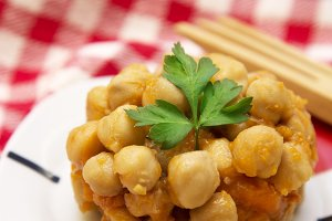 Cooked chickpeas on wooden background and red tablecloth