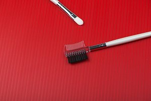 Makeup brushes on red background. Horizontal shoot.